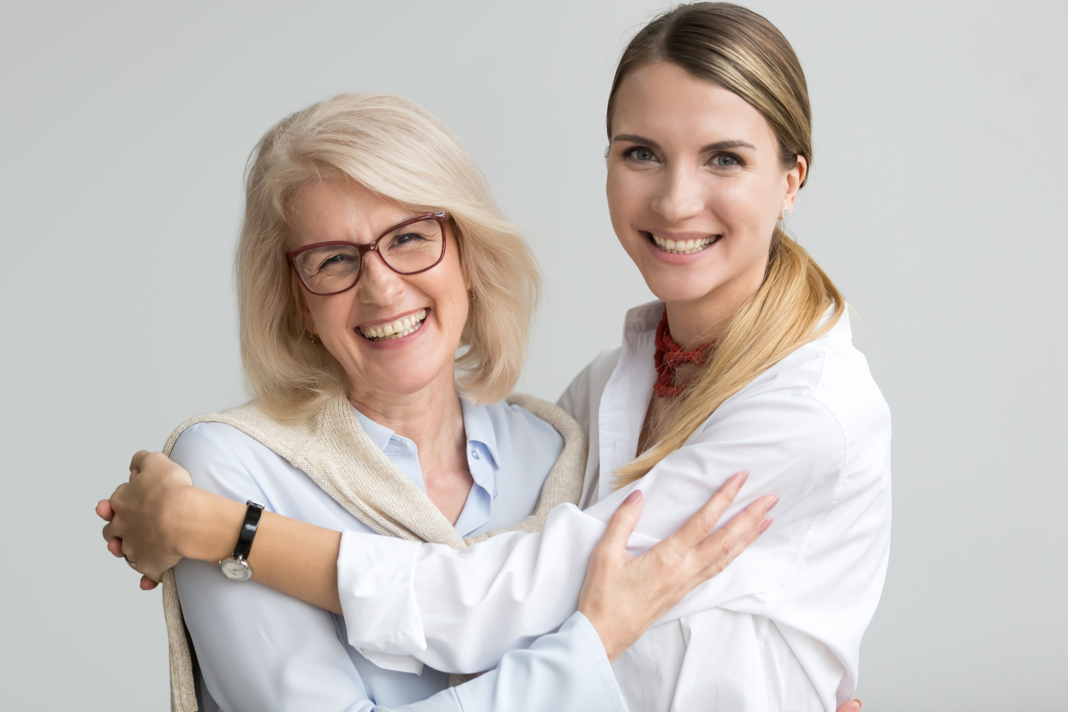 Happy attractive senior older aged mother and young adult daughter smiling laughing looking at camera, two beautiful women having fun embracing head shot portrait, cheerful family hugging concept